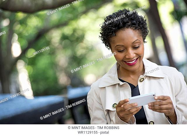City life. People on the move. A woman outdoors in the park, checking her smart phone