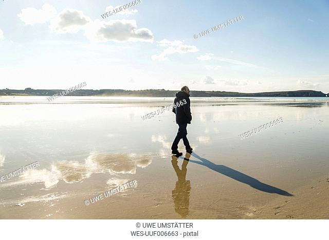 France, Bretagne, Finistere, Crozon peninsula, man walking on the beach
