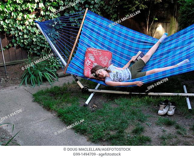 A nine year girl falls from on hammock reading after a dog approaches