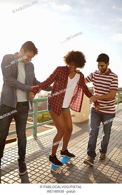 Two friends teaching a girl to skateboard on a pavement, the men holding the girl from either side so she can find her balance