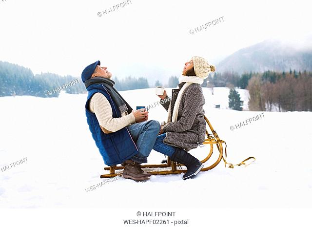 Senior couple sitting on sledge with hot beverages in snow-covered winter landscape looking up