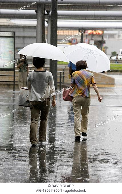Pedestrians walking in heavy rain outside Kyoto Station in Kyoto, Japan