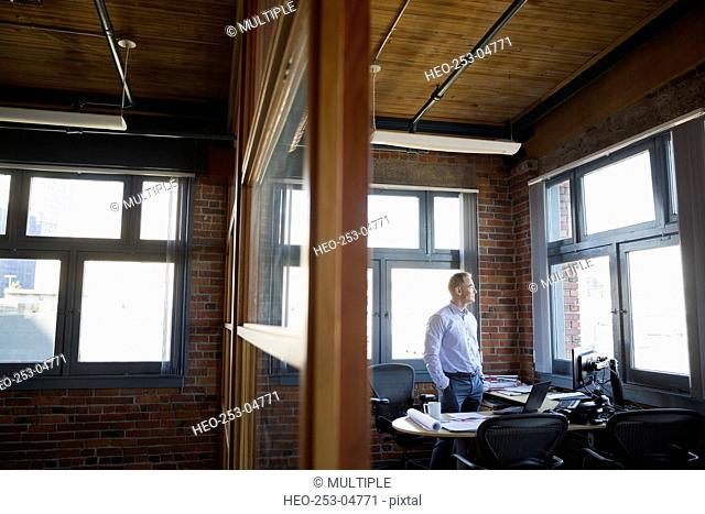 Pensive businessman looking out office window