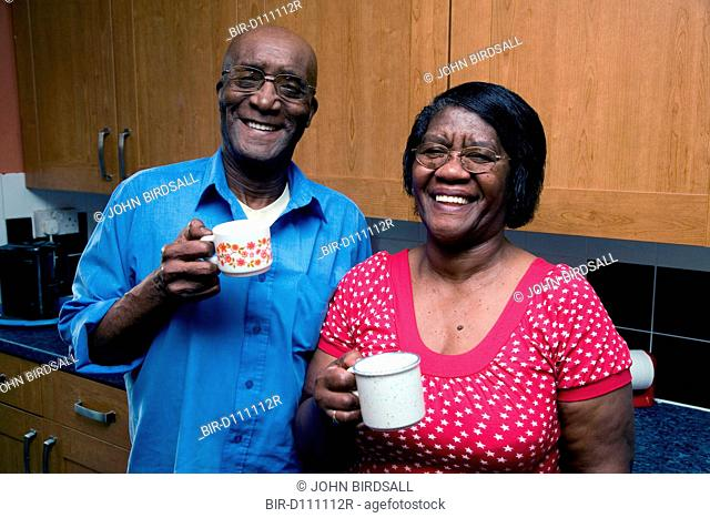 Older couple drinking tea in the kitchen smiling