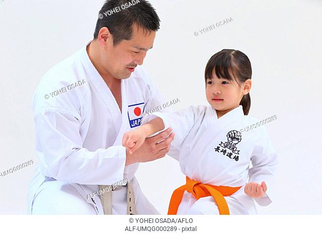 Japanese kid in karate uniform training with teacher on white background