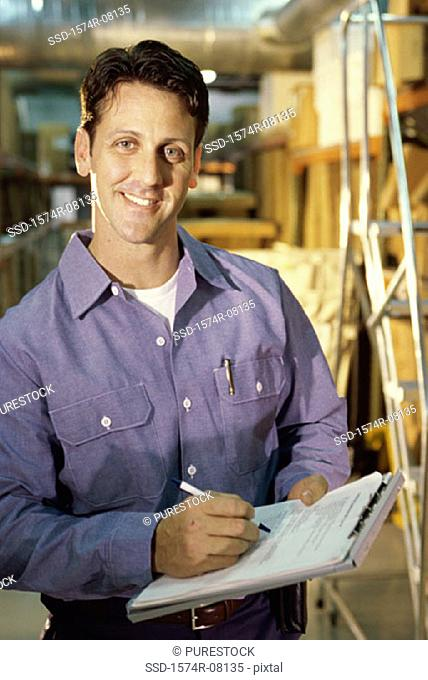Portrait of a worker holding a clipboard smiling