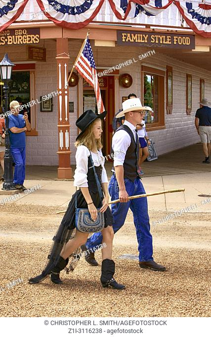 Young modern cowboy and his gal walking down E Allen St during the annual Doc Holiday event in Tombstone, Arizona