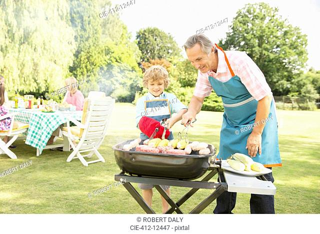 Grandfather and grandson grilling meat and corn on barbecue
