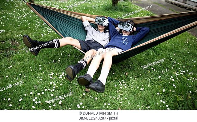 Mixed Race brother and sister in hammock wearing virtual reality goggles