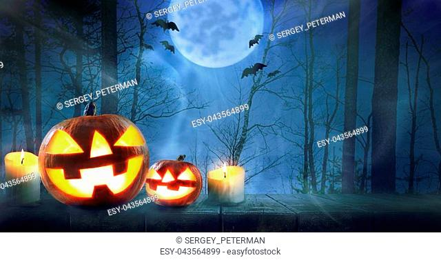 Halloween pumpkins against night scary autumn forest background