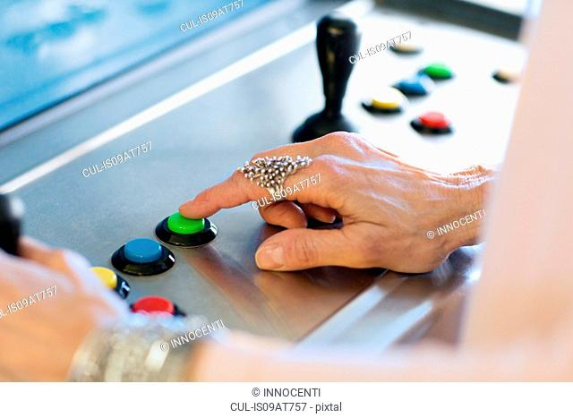 Close up of senior womans hand pressing button on games machine