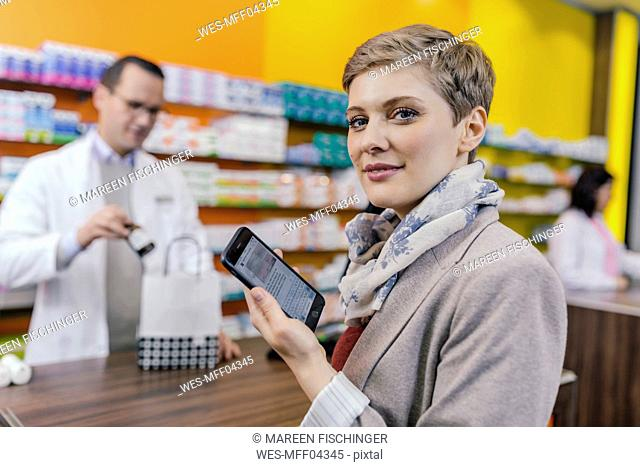 Portrait of woman with cell phone at counter in pharmacy