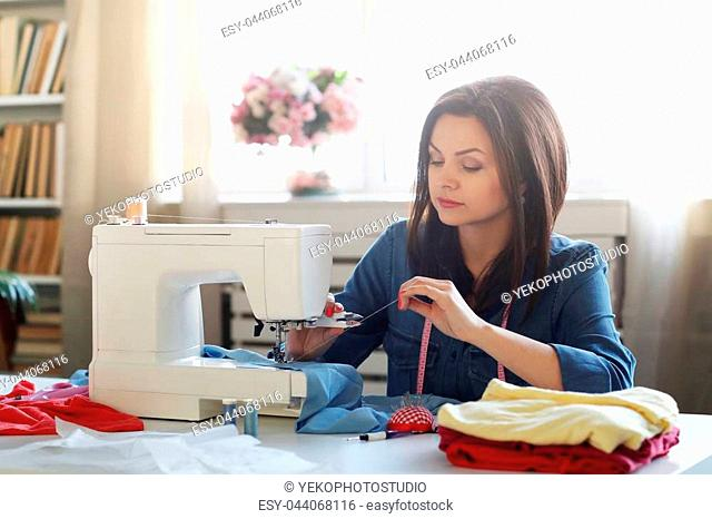 Lovely seamstress at the table