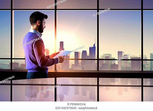 Side view of businessman examining contract in modern office interior with city view. Deal and finance concept