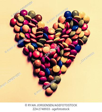 Retro filtered food photo on a merged mix of colour candy pieces forming a heart shape. Valentines day treats