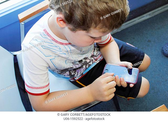 a 5 year old boy using an IPod or IPhone or cell phone