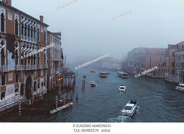 Elevated view of motor boats on misty canal, Venice, Italy