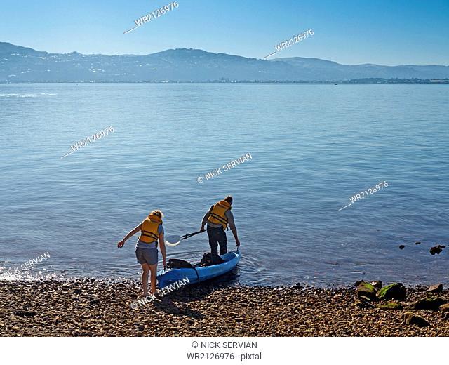 Couple launching kayak, Matiu/Somes Island in Wellington Harbour, North Island, New Zealand, Pacific