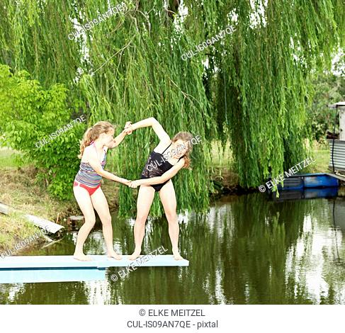 Two sisters play-fighting on diving board over lake
