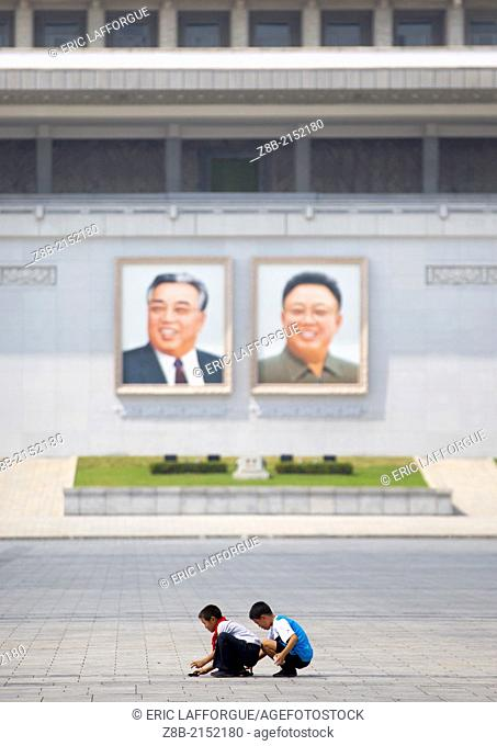 Kids Playing In Front Of Kim Il Sung And Kim Jong Il Giant Portraits On Kim Il Sung Square, Pyongyang, North Korea