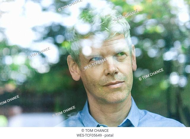 Portrait of pensive mature man looking out of window
