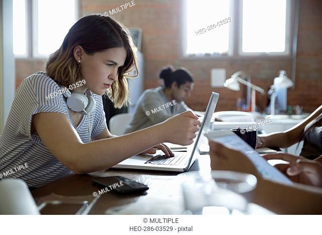 Focused designer working at laptop in office