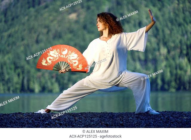 Young woman Tai Chi Quan practitioner with a red hand fan practicing Taiji Pu Bu stance in the morning sunrise by the lake in the nature