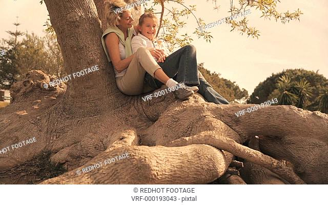 Dolly shot of grandmother and granddaughter sitting on tree root in park