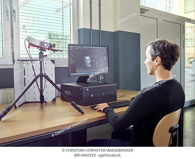 30-35 year old woman scans her head with a 3D scanner