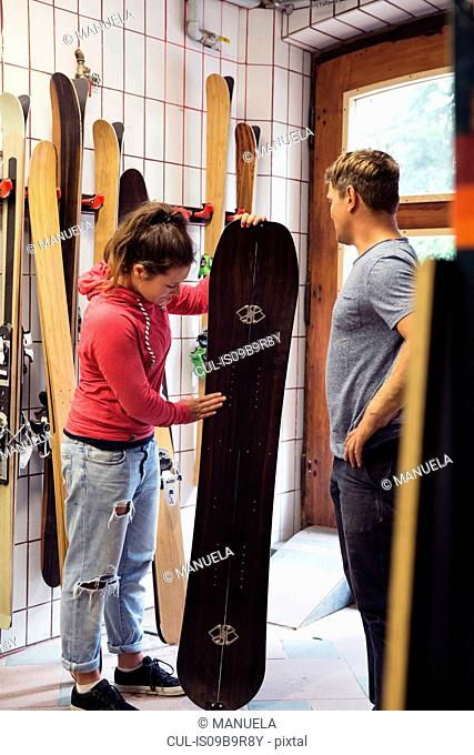 Man and woman in workshop, inspecting ski equipment