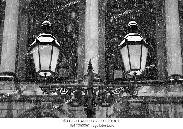 Snow falls on an old street lamp in Munich