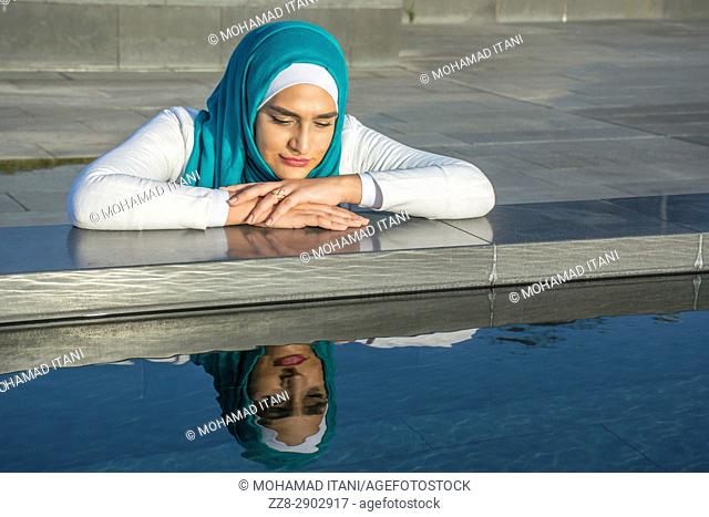 Young Muslim woman wearing hijab leaning on the pool