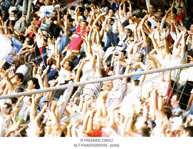 Crowd in stadium with arms in air