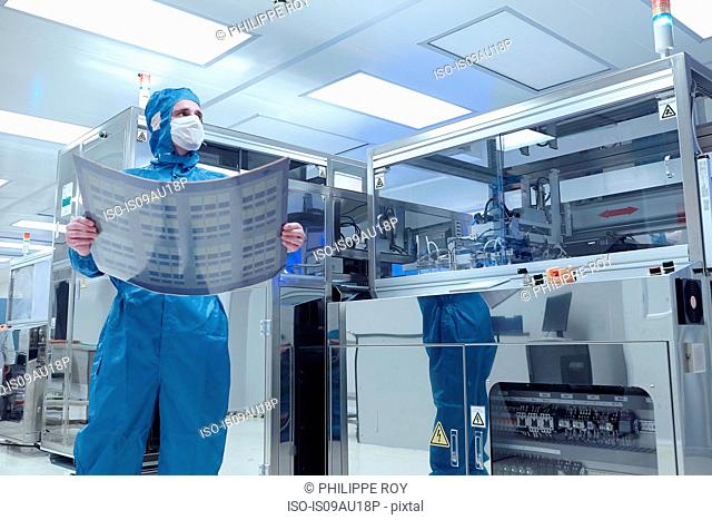 Male worker holding flex circuit in flexible electronics factory clean room