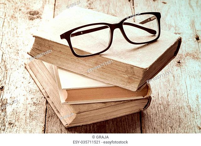 Old books and reading glasses on the wooden background