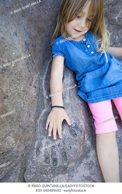 four years old girl with bracelet placing her hand on mold of adult arm in grey stone