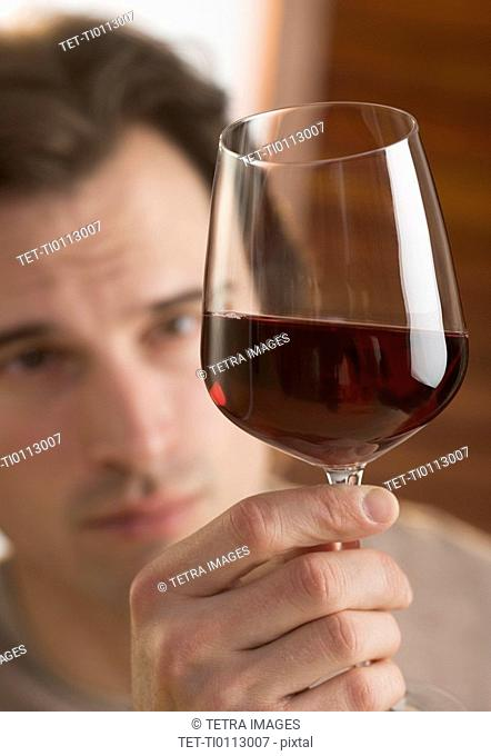 Man examining upheld glass of wine
