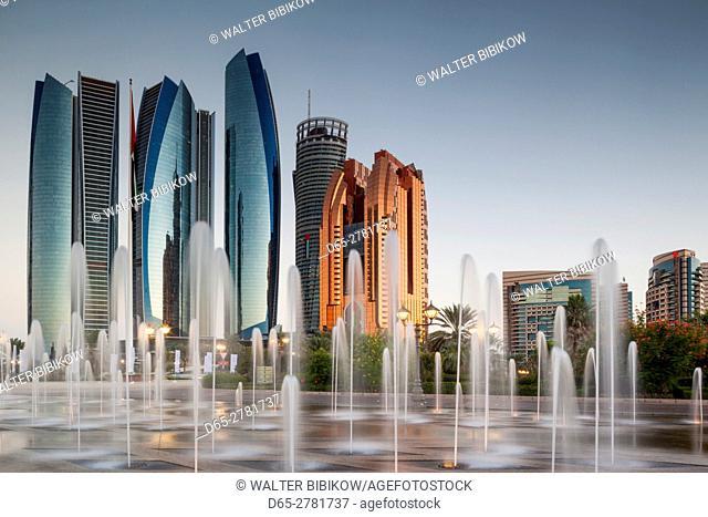UAE, Abu Dhabi, Etihad Towers and Emirates Palace Hotel fountains, dusk