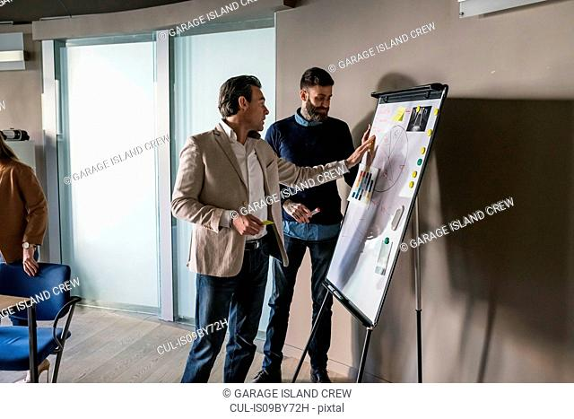 Businessmen having discussion over notes on whiteboard in office