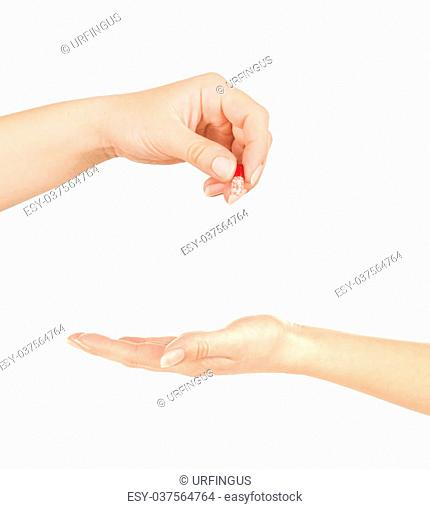 Hand giving medicine to other hand isolated