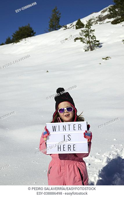 "Slogan """"winter is here"""" held by a girl in a snowy landscape"