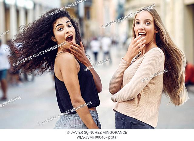 Portrait of two astonished young women on the street