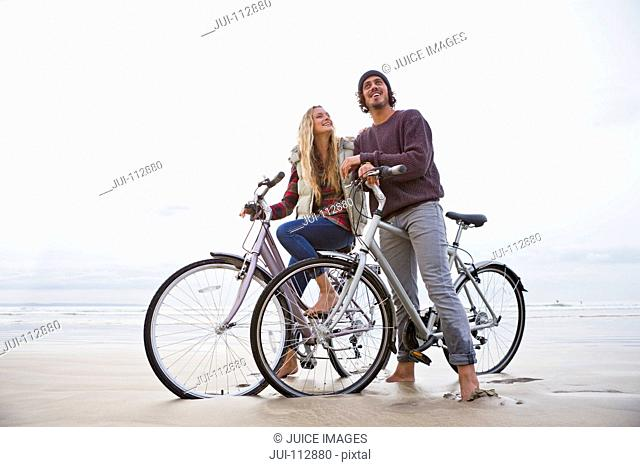 Couple with bicycles on beach