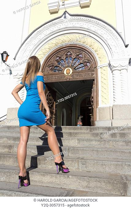 Beautiful, attractive Ukrainian woman wearing a blue dress climbing the stairs of the Orthodox Transfiguration Cathedral for a photographic sequence in Zhitomyr