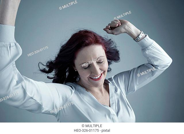 Portrait carefree Caucasian mature woman with burgundy red hair dancing with arms raised and eyes closed