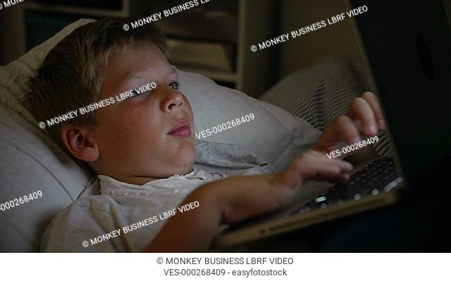 Boy in bed with face illuminated by laptop he is using.Shot on Sony FS700 in PAL format at a frame rate of 25fps