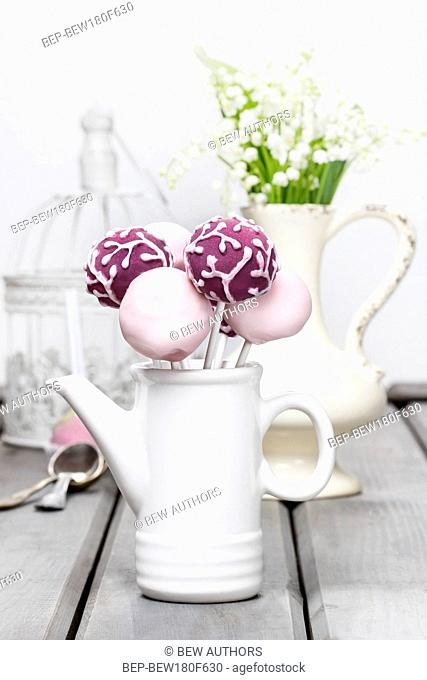Pastel cake pops on rustic grey wooden table. Bouquet of lilly of the valley flowers in ceramic vase in the background
