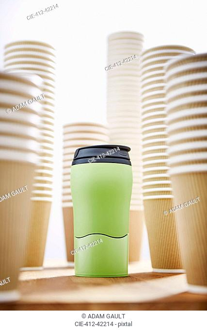 Green insulated drink container surrounded by disposable coffee cups