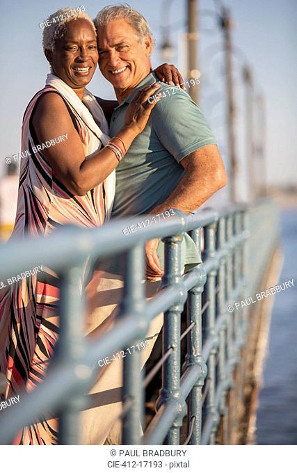 Portrait of smiling senior couple hugging on pier