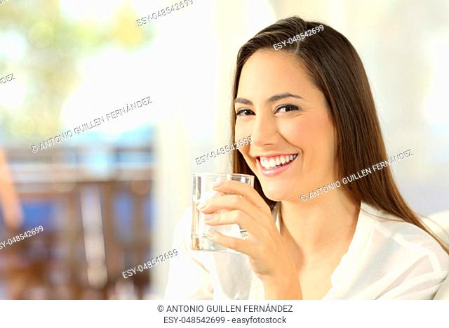 Portrait of a happy woman holding a glass of water and looking at camera sitting on a sofa in the living room at home